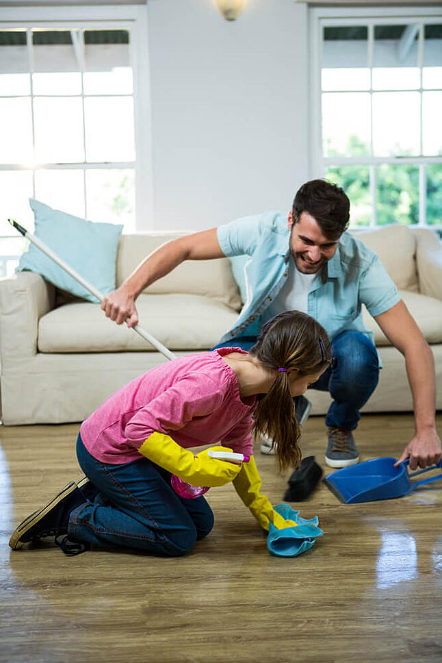 Daughter helping father to clean floor at home